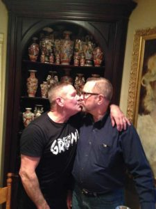 Tom and Pete kiss in their Mill Hill Home. Photo by Gary Nigh.