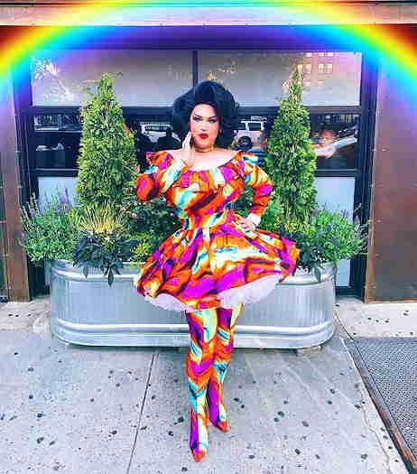 Jasmine Rice LaBeija with standing with rainbow above her head