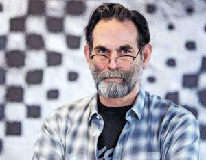 Avram Finkelstein posing with his art behind him