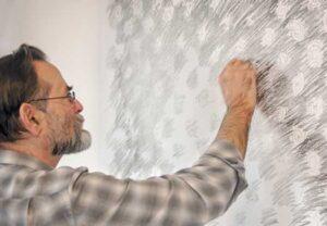Avram Finkelstein posing with his art