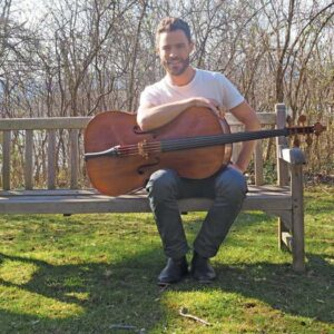 Branden James sitting on bench with a cello