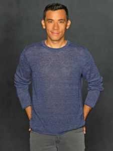 Conrad Ricamora is relaxed in a blue sweater