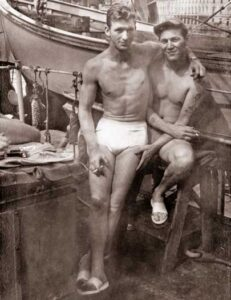 """Photo of two men in swimsuits from the book """"Loving: A Photographic History of Men In Love"""""""
