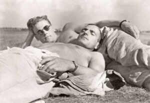 """Photo of two men on a beach from the book """"Loving: A Photographic History of Men In Love"""""""