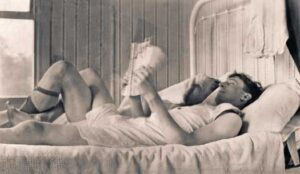 """Photo of two men on a bed from the book """"Loving: A Photographic History of Men In Love"""""""