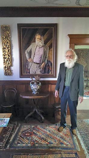Norm Larson stands in front of a portrait of himself