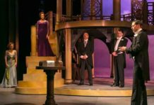 """The Merchant of Venice"" at The Shakespeare Theatre of NJ. In the foreground: John Keabler as Bassanio. Pictured in background from left to right: Rachel Towne as Nerissa, Melissa Miller as Portia, Joe Penczak as Tubal, Ian Gould as Gratiano. Photo by Jerry Dalia."