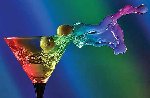 Rainbow colored glass with cocktail with olives