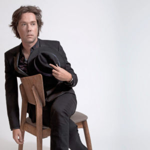 Rufus Wainwright sitting in a chair