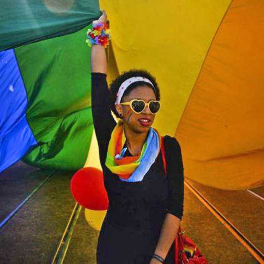 Black woman under large rainbow colored flag