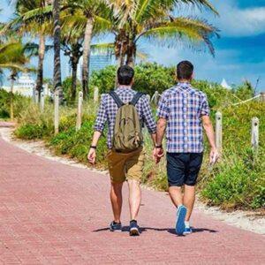 Gay couple walking along the beach in Miami