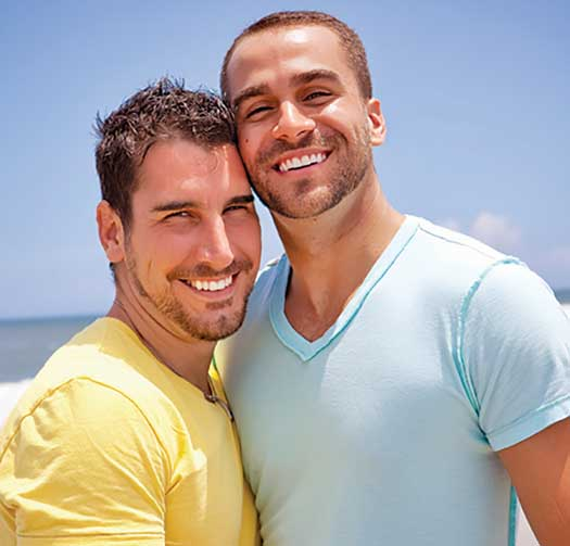 Young gay male couple on beach