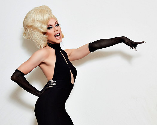 Alaska Thunderfuck wearing a black dress and pointing to the right