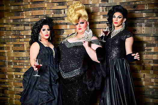 Three Drag Queens dressed in black and holding cocktails.