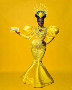 Bob the Drag Queen wearing a yellow gown holding a purse to the left