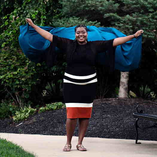 Cassandra Alfred holding a blue scarf in the air