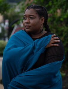 Cassandra Alfred wrapped in a blue scarf