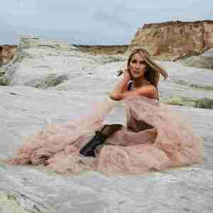 Celine Dion on the beach wearing a pink dress