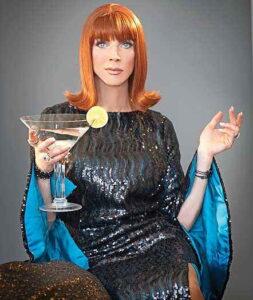 Coco Peru holding a large martini