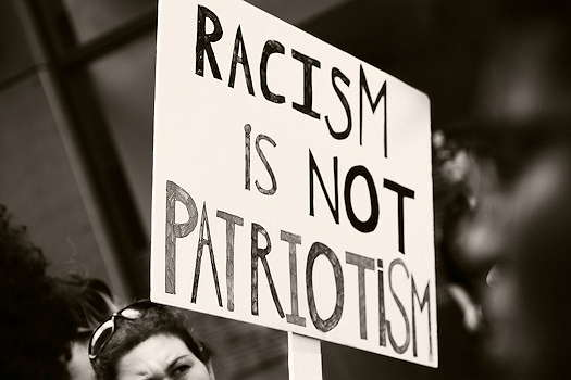 Picketer holding a sign that says Racism is not Patriotism
