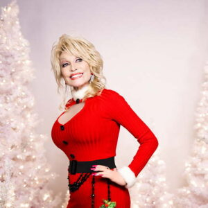 Dolly Parton wearing a tight red sweater