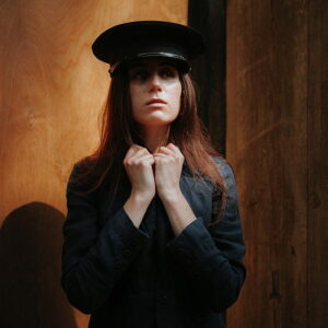 dodie wearing a black military style hat