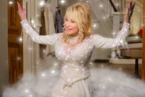 Dolly Parton wearing a white shimmery dress