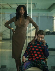 Dominique Jackson standing next to a man in a chair