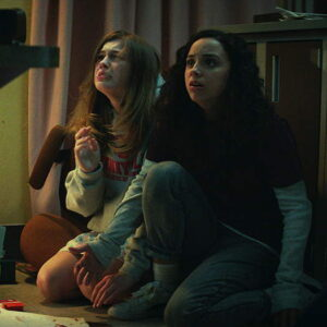 Two women kneeling on the floor and looking scared