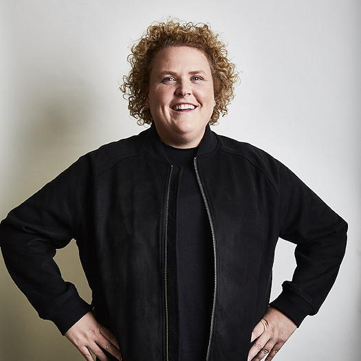 Fortune Feimster wearing a black jacket and standing with both hands on her hips