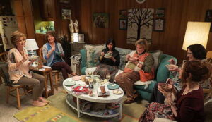 Fortune Feimster sitting in a living room with a group of women