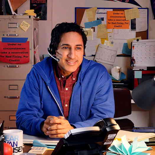Maulik Pancholy sitting at a cluttered desk