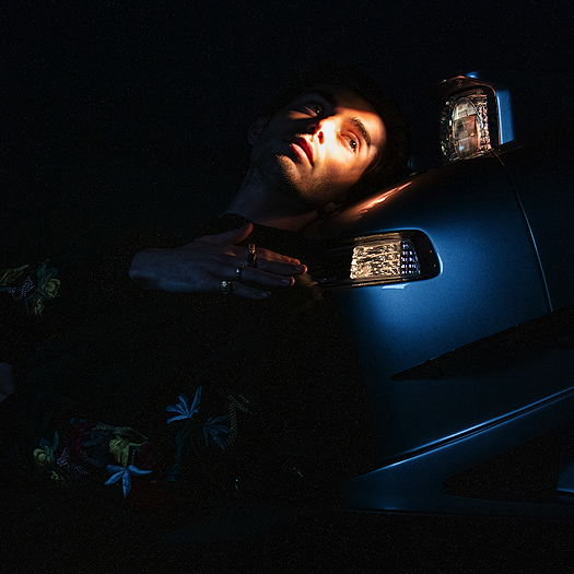 Greyson Chance leaning against a car near the headlight while in the dark