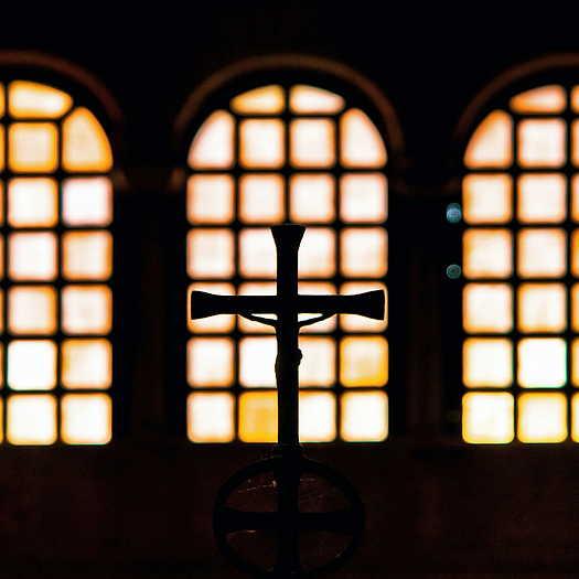 Silhouette of a cross inside a church