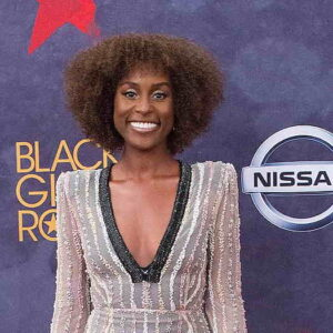 Issa Rae 2017 smiling and wearing a low cut silver dress