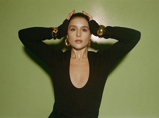 Jessie Ware wearing a black dress with a green background