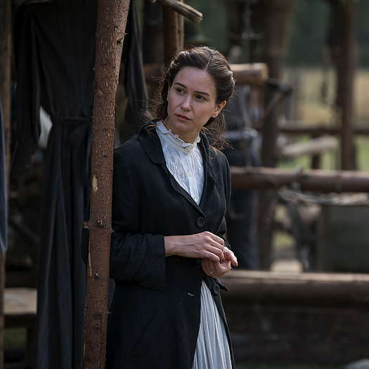 Katherine Waterston standing outside on a farm