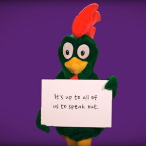 """Cornelius holding a sign that says """"It's up to all of us to speak out."""""""