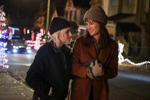 """""""Happiest Season"""" scene with two women walking down the street, Christmas lights in background"""