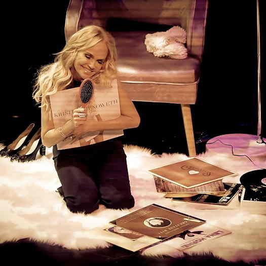 Kristin Chenoweth kneeling on white carpet hugging albums