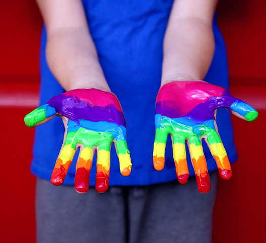 Young child with a rainbow painted on both hands
