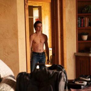 Young man standing in doorway, shirtless.
