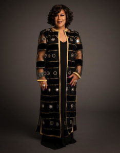Martha Wash standing, wearing a black and brown dress