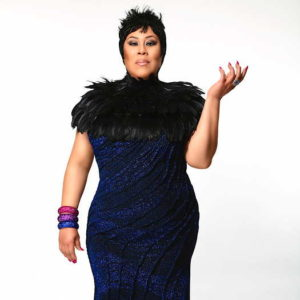 Martha Wash wearing black and blue dress with black feather collar