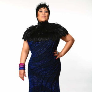 Martha Wash wearing black and blue dress, standing with her hand on her hip