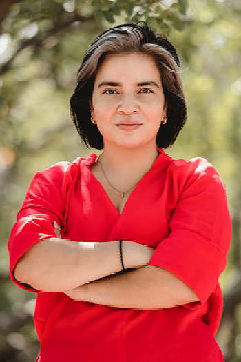 Mayra Hidalgo Salaza standing outside, wearing a red shirt with her arms crossed.