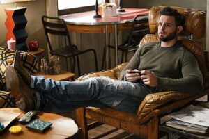 Nico Tortorella sitting in a chair playing a video game