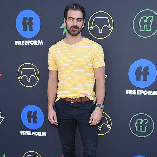 Nyle DiMarco standing in front of a Freeform step banner and wearing a yellow polo shirt and dark pants.