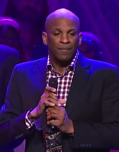 Pastor Donnie McClurkin holding a microphone