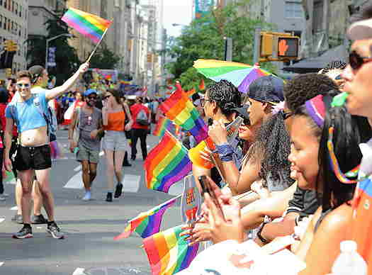 People at pride parade holding rainbow flags